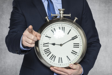 businessman with clock pointing at you