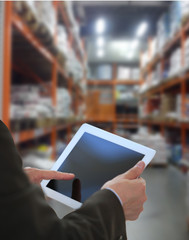 Businessman checking inventory in market on tablet computer