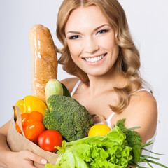 Portrait of woman with vegetarian food, on grey