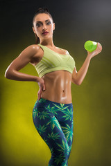Sports woman is engaged in fitness on a black background