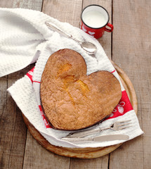 breakfast cake inside heart baking tin over wood with vintage si