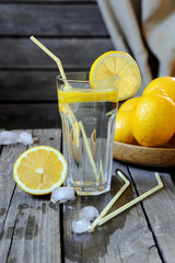 Lemonade in a transparent glass and lemons on a  wooden table