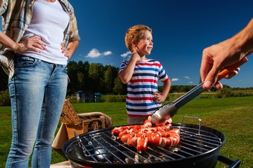 Young family preparing sausages on a grill outdoors