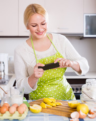 Girl with smartphone at kitchen