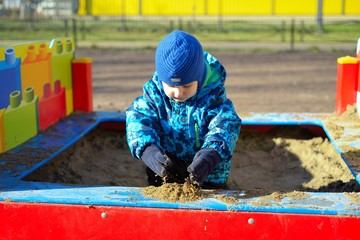 The small child plays in a sandbox
