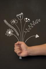 holding flowers on blackboard