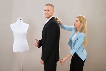 Female Tailor Taking Measurement Of Man's Suit