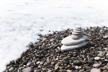 The pyramid of pebbles on the beach in sea foam