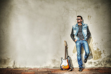 man and guitar against a grungy wall in hdr