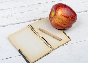 Apple and notebook on a table