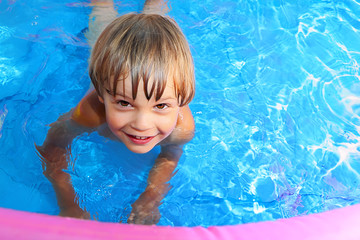 Kid swims in the pool.