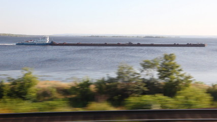 barge pushing cargo on wide river both flashing trees and railway