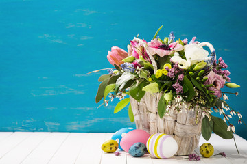 Basket of flowers and easter eggs on a wooden background with sp
