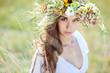 Beautiful woman in a summer field with flower wreath