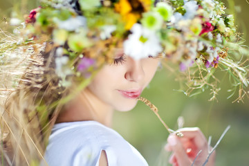 Beautiful woman in a summer field with flower wreath