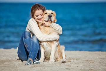 girl are playing with a dog on the beach