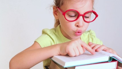little girl merrily reads book, leads look, moves lips