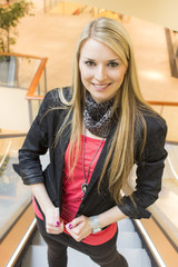 Junge attraktive Frau auf einer Rolltreppe