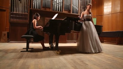 Review woman pianist playing piano and opera singer on stage