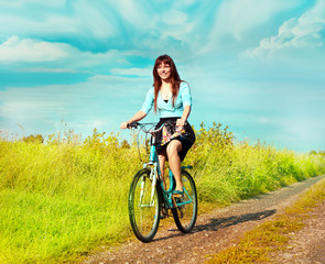 Happy  woman rides a bicycle on a summer meadow