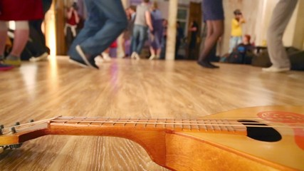 Wooden guitar lies on floor and legs of dancing people move