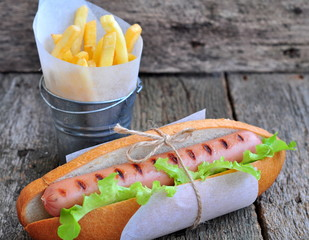 Hot dog with fresh lettuce and french fries on a wooden table