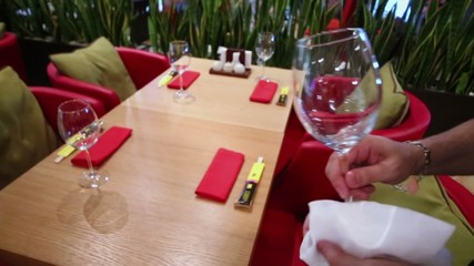 Man cleans wine glass and puts it on table in cafe