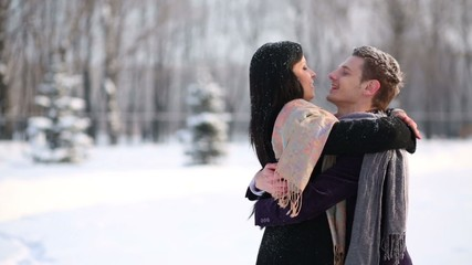 Young man and woman stand in scarves in winter park and embrace