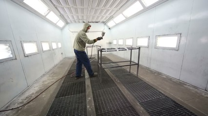 Worker in protective clothes works in paint-spraying booth