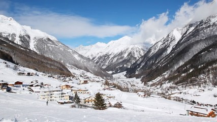 Houses stand in valley under blue sky in sunny weather