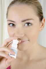 Frau mit Nasenspray gegen Schnupfen