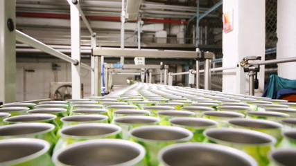 Rows of empty cans moving on conveyer line in large brewery