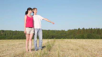 guy holds girl by hand in field and shows to it afar
