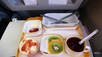 Passengers hand takes glass of juice from table in plane
