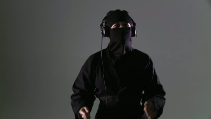 Ninja wearing headphones and dancing against a grey background.  Midshot that develops into a medium close up.