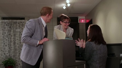 Office workers celebrate a successful deal, then the female boss slaps her male co-worker's backside.  He leaves and she plays it up with a female colleague.  Camera mounted on moving jib arm.