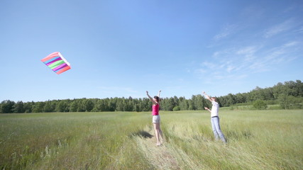 guy flies kite in field, and girl nearby rejoices and claps