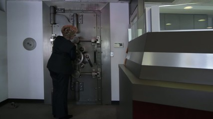 Woman opens a large bank vault door revealing the safe deposit boxes inside.  Wide shot with camera on slider.
