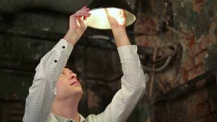 Handsome man in white shirt changes light bulb at old lamp