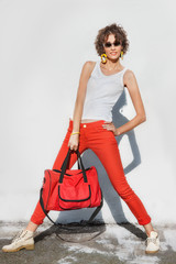 Stylish young woman in red jeans with bag