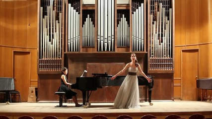 Woman pianist plays the piano and singer emotionally sing