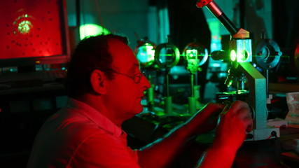 scientist who is adjusting microscope in system of lasers and carrying-out glasses