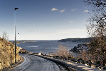 Asphalt road, gravel sprinkled over the fjord.