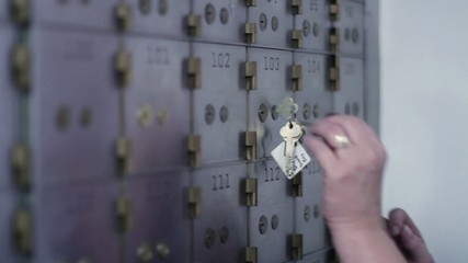 Woman opens up a safe deposit box and removes contents.  Big close up inside bank vault, camera mounted on slider.