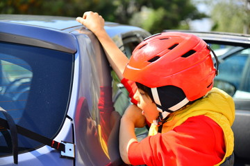 Car rear bicycle rack and a kid with helmet