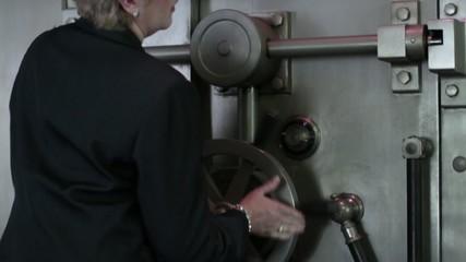 Woman opens a large bank vault door.  Close up.