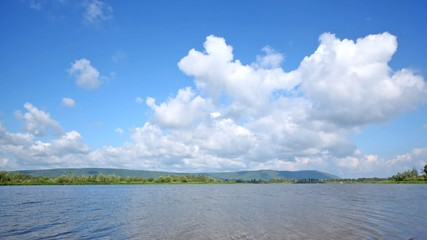 Clouds fly on blue sky over river in sunny weather