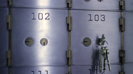 Woman unlocks a safe deposit box and removes contents, then replaces them and closes door again.  Detail shot inside bank vault, camera mounted on slider.