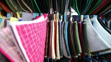 Rows of colored mats under horses saddle in specialized shop