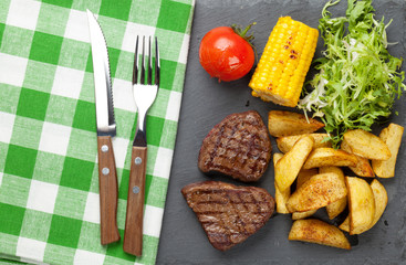 Steak with grilled potato, corn and salad